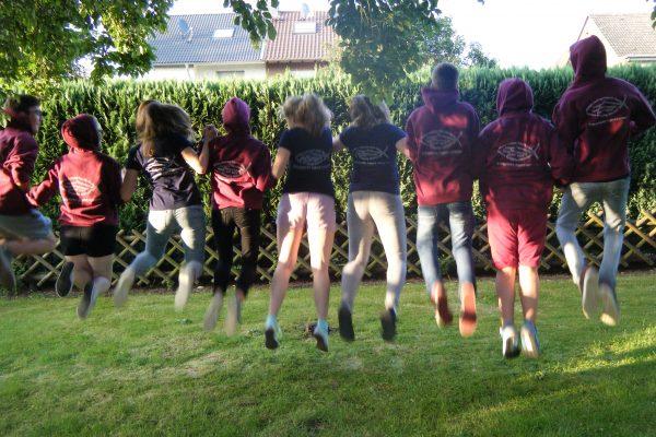 Jugendliche, die Teamkleidung tragen und hochspringen